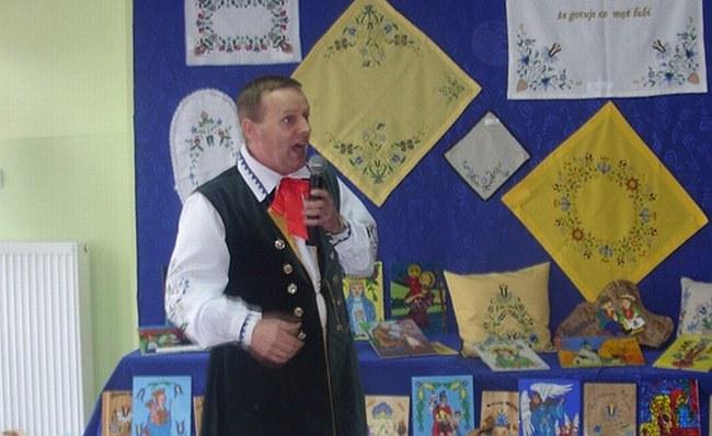 Zdj. Stanisław Gostomczyk – gawędziarz kaszubski z Lipnicy. W  tle wystawa prac wykonanych przez uczniów miejscowej szkoły prac .